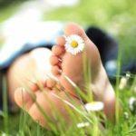 Ein Paar Füße mit einem Gänseblümchen