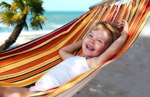 Lachendes Kind am Strand in einer Hängematte