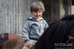 Kleiner Junge lacht beim Reiten.