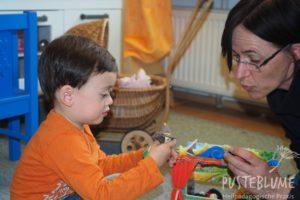 Gesine Herzog spielt mit einem kleinen Jungen mit Fingerpuppen.