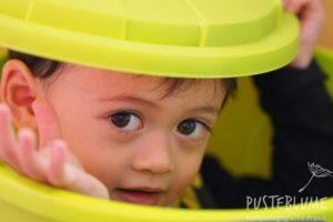 Kleinkind schaut aus einem Eimer mit Deckel heraus.