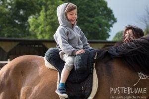 Ein Junge sitzt lachend auf dem Pferd.